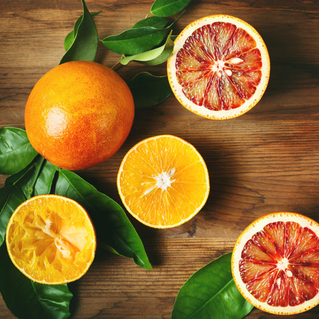 Different sort of orange fruit on wooden table. Top view. Instagram color effect. Stock Photo