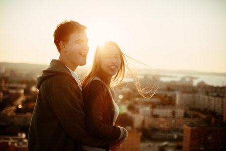 romantic hug: Sunny outdoor portrait of young happy stylish couple hugging on the roof at sunset. Man and woman laughing and having fun.