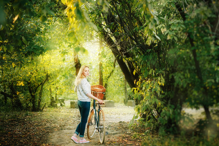 young woman: Young blonde woman on a vintage bicycle in the park in sunset. Selective focus. Stock Photo