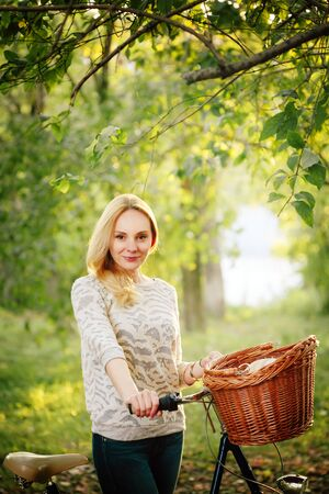 Young blonde woman on a vintage bicycle in the countryside in subset. Selective focus. Stock Photo