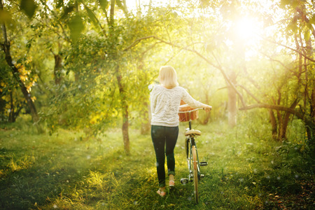 country life: Blurred iabstract mage of female back with a vintage bicycle in the park in sunset Stock Photo