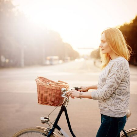city bike: Young blonde woman on a vintage bicycle in the sunset.   Selective focus.