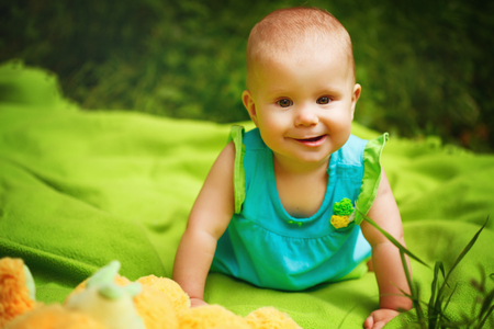 Funny Toddler Baby Girl playing in the Park. Sitting on the blanket, smiling, looking to Camera. photo