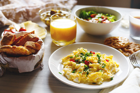 colazione: Colazione da tavolo con le uova strapazzate, pane fresco, succo d'arancia nel sole del mattino a casa. Messa a fuoco selettiva.