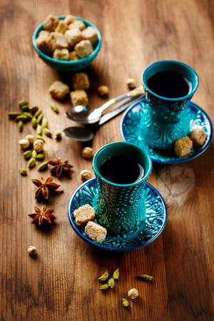 vin chaud: Thé ou le vin chaud avec diverses épices dans Lunettes traditionnels turcs sur fond de bois. Mise au point sélective. Banque d'images