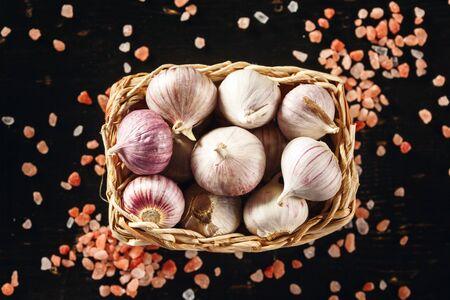 bulbet: Garlic Close Up in a Basket with Pink Himalayan Salt on Dark Background. Top View, Selective Focus. Stock Photo