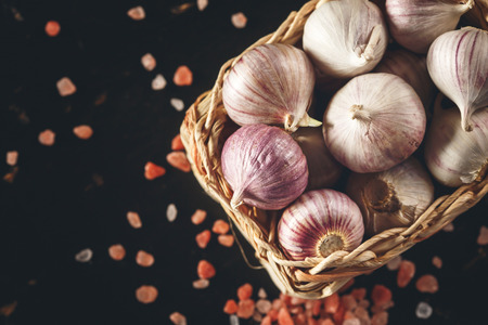 bulbet: Garlic with Pink Himalayan Salt  Close Up on Dark Background. Top View, Selective Focus. Copy Space for Your Text. Image toned.