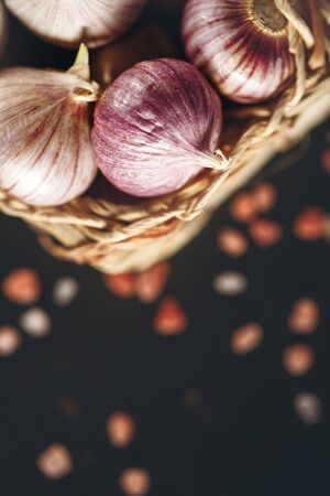 bulbet: Food Background with Garlic Close Up in a Basket on Dark Surface. Top View, Selective Focus, Shallow Depth of Field. Space for Text. Stock Photo