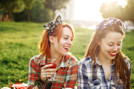 laughs: Two Young Happy Girls in Pin-Up Style on Picnic, Laughing, Drinking Wine, Having Fun. Selective Focus.