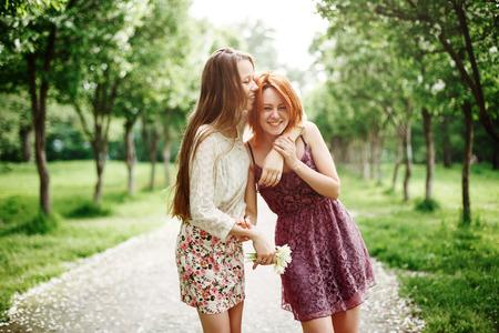 夏の公園で楽しんで二人の若い幸せな女の子。最高の笑いと受け入れの友人。