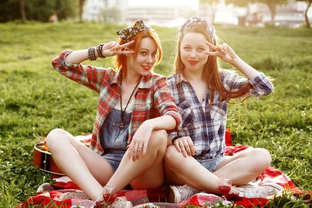 chicas divirtiendose: Dos Sonriente joven inconformista chicas se divierten en un picnic en el Parque de la puesta del sol Foto de archivo