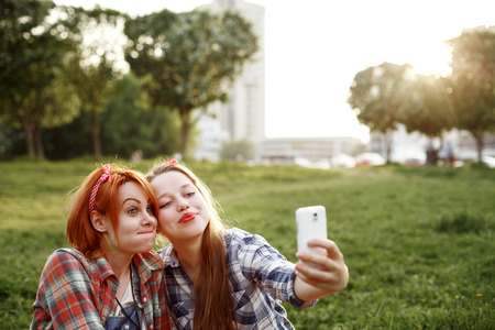 Two Young Hipster Girls Having Fun and Taking Photos (Making Selfie) on Smartphone in a Summer Park at the Sunset. Space for Your Text.