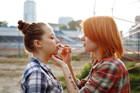 color hair: Makeup Artist Applying Red Lipstick on Lips of a Beautiful Woman. Pin Up Style.