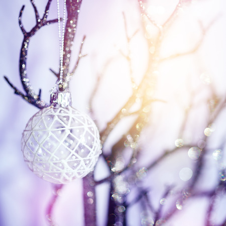 Christmas Background with Bauble on Silver Branch. Shallow Depth of Field, Selective Focus. Bokeh Lights. Festive Mood.