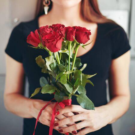 mujer con rosas: Retrato de la manera borrosa de la mujer joven sensual morena la celebración de ramo de rosas rojas. Selectivo se centran en las flores.