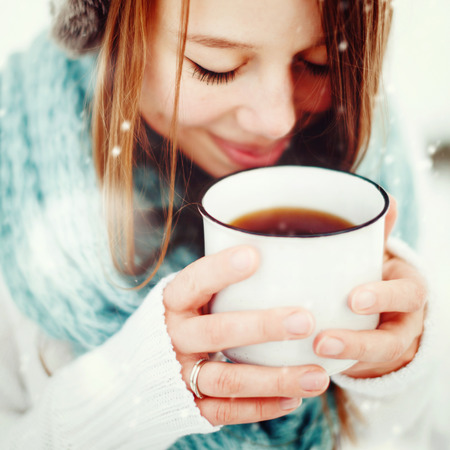Young Beautiful Female Drinking Hot Drink Outdoors in Winter. Close Up Headshot. Drawn Snow. Selective Focus.
