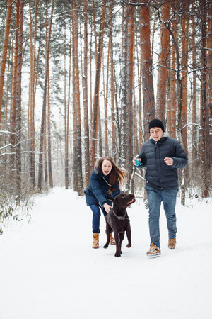 Young Couple with a Dog Having Fun in Winter Forest on Vacations. Selective Focus. Lifestyle of Happy Modern Family. Standard-Bild