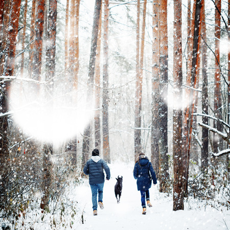winter season: Young Family Having Fun with a Dog in Winter Forest on Vacations. Copy Space for Text. Selective Focus.