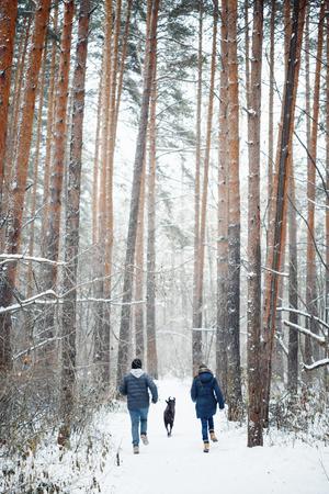 mujer con perro: Familia joven que se divierte con un perro en el bosque de invierno en Vacaciones. Copiar espacio para el texto. Foco.