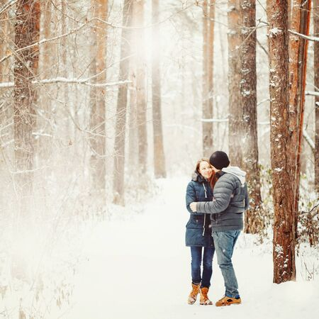 Young Couple Embracing in Winter Forest. Winter Vacations. Weekend Getaway. Space for Text. Natural Colors, Selective Focus.