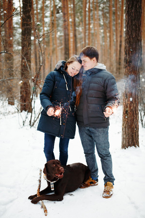 beautiful boy: Happy Couple with Dog Labrador Retriever Enjoying Winter Evening with Festive Sparklers for Christmas Time Stock Photo
