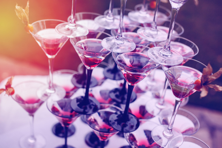 wedding reception decoration: Pyramid of Champagne Glasses with Color Cocktails. Wedding Reception. Selective Focus.