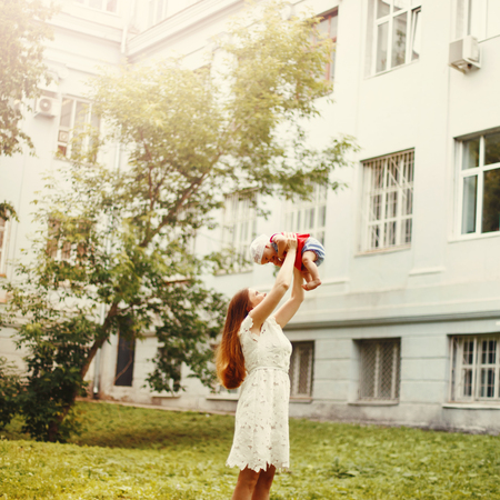 Young Happy Mother in White Dress Holding Her Baby Overhead. Selective Focus. Summer Time. Space For Text. Image Toned. Stock Photo