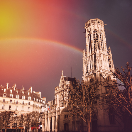 gothic architecture: Romantic Paris. View on the Church of Saint-Germain lAuxerrois with Rainbow after Rain. Historical Gothic Architecture. Stock Photo