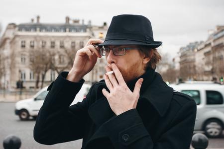 hombre con barba: Atractivo hombre con barba que desgasta el sombrero de fumadores en la calle en la ciudad europea. Enfoque diferencial, grano a�adido.