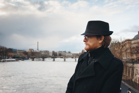hombre con barba: Serious Pensive Bearded Man Wearing Hat in Paris, France, Walking near Seine River. Headshot Composition, Space for Text.