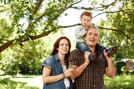 屋外を歩いて幸せな家族。妊娠中の女性、人および男の子の父の上に座って。楽しんでください。家族の価値観の概念。自然な色。