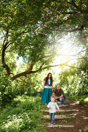 Happy Family Spending Time Together Outdoors. Pregnant Woman, Man and Cute Little Boy. Natural Colors. Selective Focus on a Kid. Sunshine Flare. Stock Photo