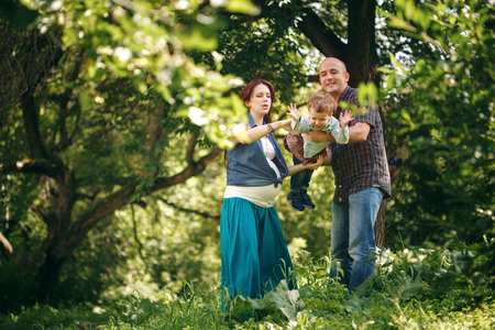 Happy Young Parents Playing with Their Son in the Park. Family Clothing Style. Natural Colors. Stock Photo