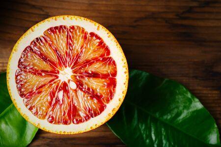 citricos: Madura jugosa Mitad de una c�trica Naranja de cerca sobre fondo de madera. Colores vibrantes. Foto de archivo