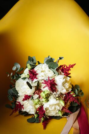 luxuriant: Luxuriant Wedding Bouquet of Different Flowers in Rustic Style on Bright Yellow Background. Empty Space for Text. Selective Focus.