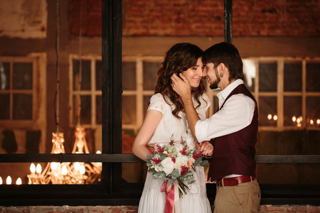 loft interior: Happy Stylish Wedding Couple, Groom and Bride with Flowers, Standing Together Embracing and Kissing. Loft Interior. Stock Photo