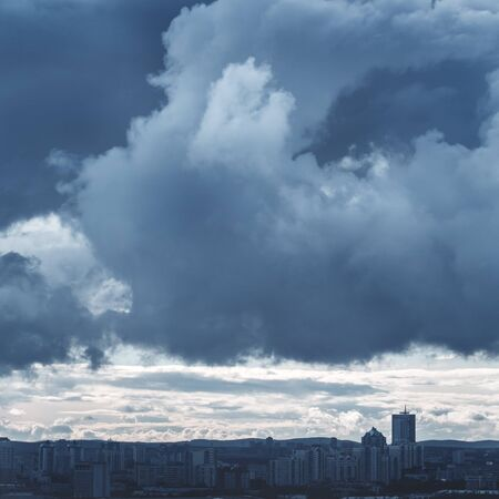 moody: Monochrome Landscape with Stormy Sky and Industrial City. Image Toned with Blue Colors. Moody Background. Stock Photo