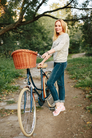 full height: Young Happy Woman on Vintage Bicycle with Basket in Park at the Sunset. Full Height, Neutral Colors. Stock Photo