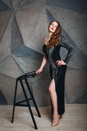 stage make up: Full Body Portrait of Beautiful Young Red Hair Woman Looking at Camera in Luxury Black Dress with Stage Make Up. Model Standing Against Dark Grey Background.