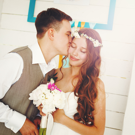 Emotional Moment of Wedding Day. Beautiful Newlywed Couple. Groom Kissing His Bride. Image Toned with Vintage Colors.