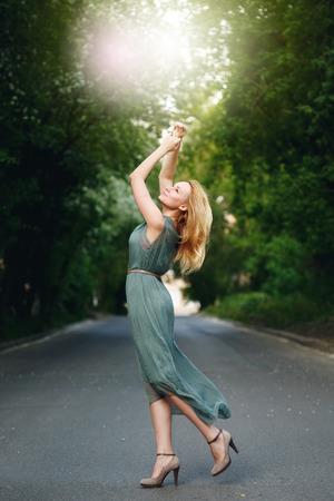 Magnifique danse jeune femme sur la route Alone in Summer Evening. Féminité Concept. Banque d'images