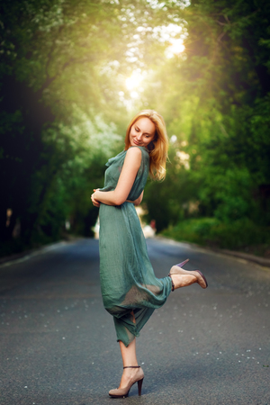 femininity: Wonderful Young Woman Dancing on the Road Alone in Summer Evening. Femininity Concept. Stock Photo