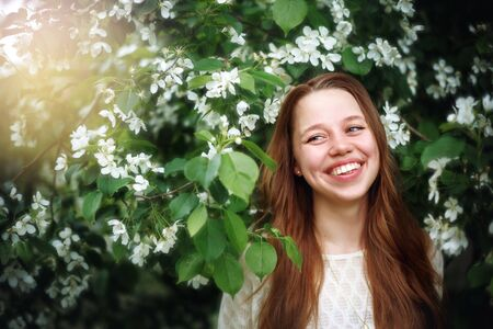 enjoying life: Headshot Portrait of Beautiful Young Woman among Spring Flowers at the Nature. Female Laughing and Enjoying Life and Moment.