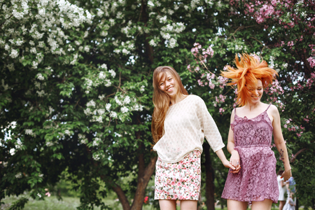 girls having fun: Two Young Pretty Girls Having Fun Outdoors in Summer Park. Freedom Youth Concept. Happy Woman Laughing and Jumping. Stock Photo