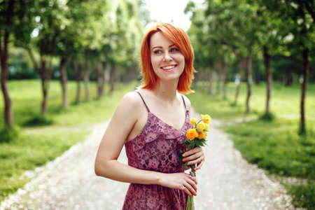 enjoying life: Portrait of Beautiful Young Red Heair Woman Holding Spring Flowers at the Nature. Female Laughing and Enjoying Life and Moment.