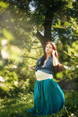 full height: Beautiful Pregnant Woman in Blue Dress Enjoying Nature and Sun in Green Summer Park. Full Height Portrait, Looking in Camera.