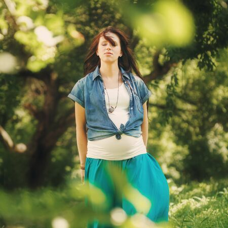 full height: Pregnant Woman Meditating at the Nature. Full Height Portrait, Eyes Closed. Selective Focus. Image Toned.