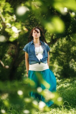 full height: Pregnant Woman Meditating at the Nature. Full Height Portrait, Eyes Closed. Selective Focus.