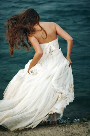 dress blowing in the wind: Full Body Rear View of Woman with Long Hair in White Dress Standing near Stormy Sea. Blowing Wind Hair. Selective Focus. Grain Added for Best Impression.