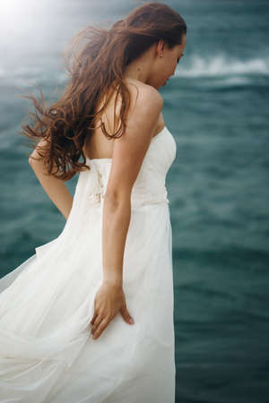 dress blowing in the wind: Beautiful Woman in White Dress Standing near Stormy Sea. Blowing Wind Hair. Selective Focus. Grain Added for Best Impression.